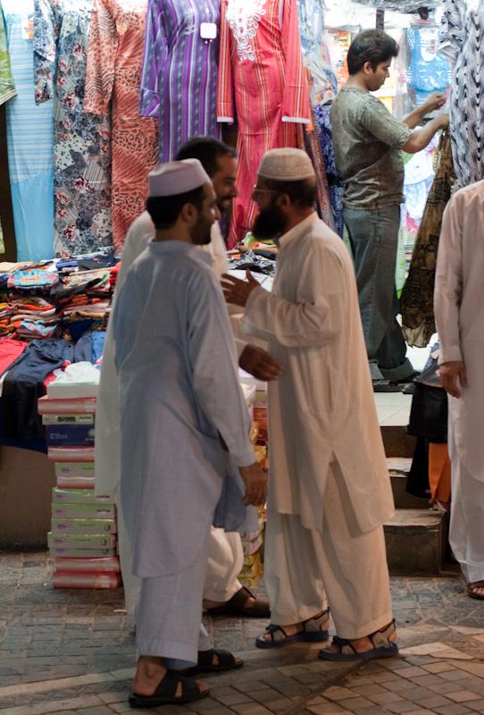 Omanske menn i omanske klær handler i en omansk suq